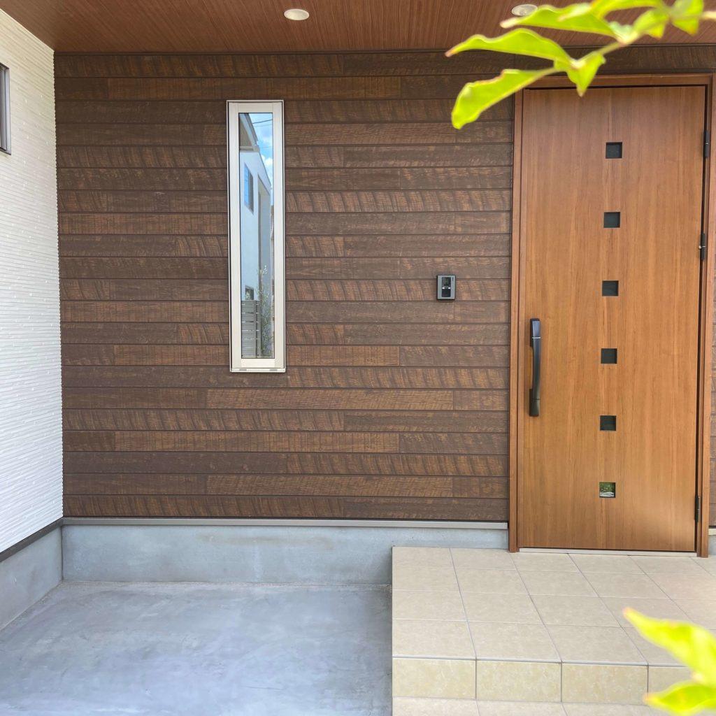 武雄市武雄町新築建売住宅「OURS武雄富岡3号地」◆玄関外壁材はニチハ キャスティングウッドのミディアムブラウンMGと、ニチハ モナビストーンのフローMGホワイトです。玄関前には緑が映える植栽があります。